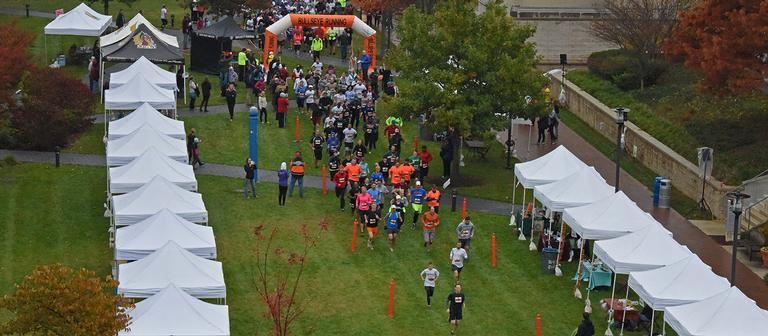 Overhead of racers through starting gate on campus quad for 5K Challenge Race 2015