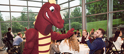 Duncan the Dragon giving a student a high five.