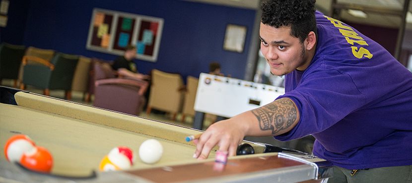 Student playing pool in Game Room