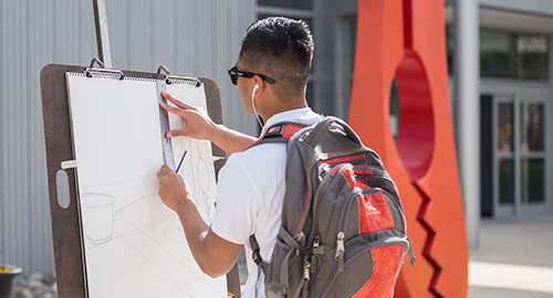 Photo of student drawing outside of HPVA. Link to Arts and Humanities Academic Programs