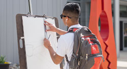 A student drawing on campus.